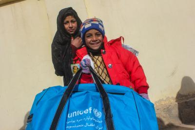 A boy receiving winter emergency kit