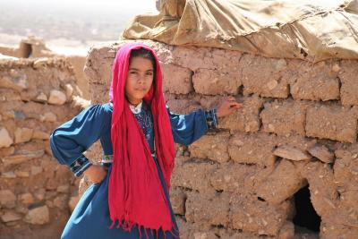 A girl stands outside her house in Herat, Afghanistan.