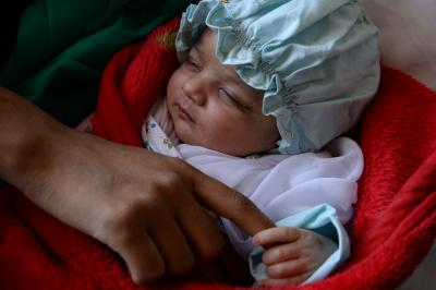 A mother holds her two days old son's hand after giving birth in the Herat Maternity Hospital in western Afghanistan.