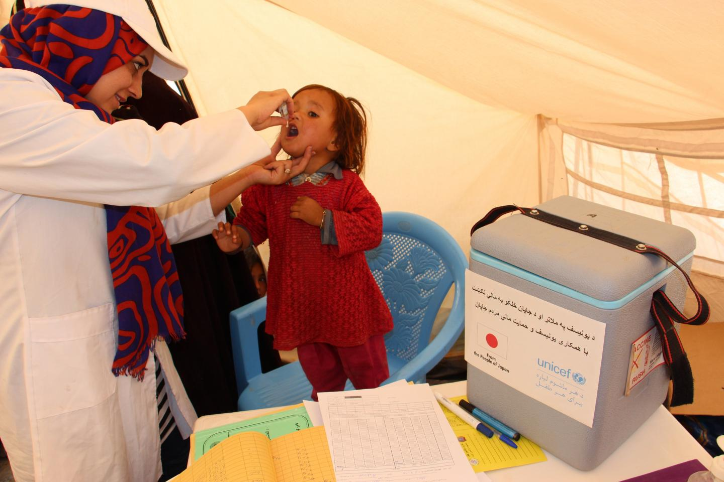 Khadija, 2 years old, being vaccinated in Herat, Afghanistan.