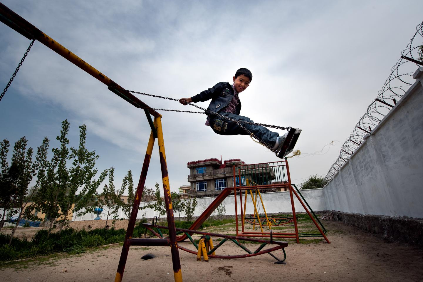 A boy swings on the playground of a day care centre in Kabul, Afghanistan.