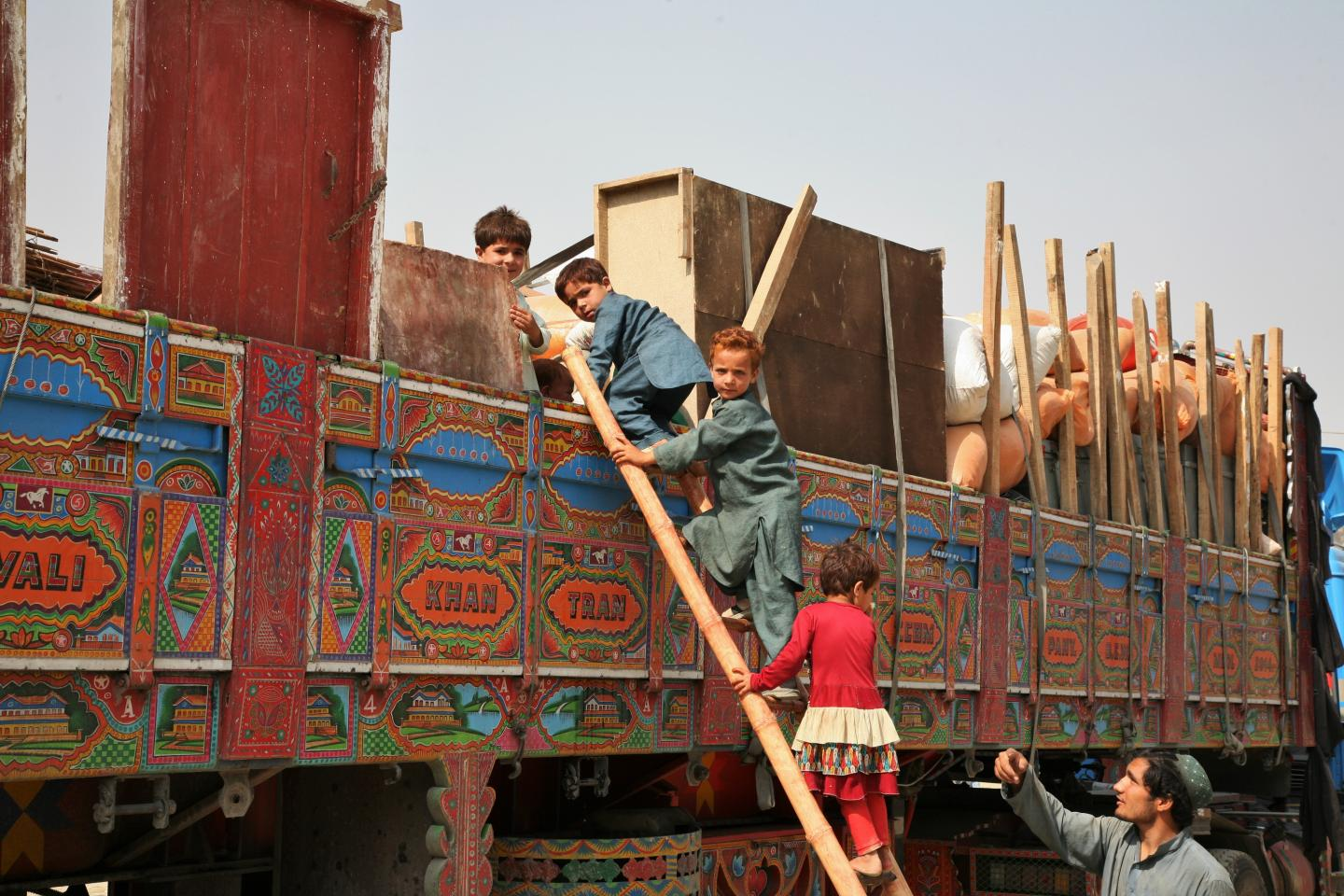 Afghan returnee children use a wooden ladder to board a truck near the Torkham border crossing between Afghanistan and Pakistan.