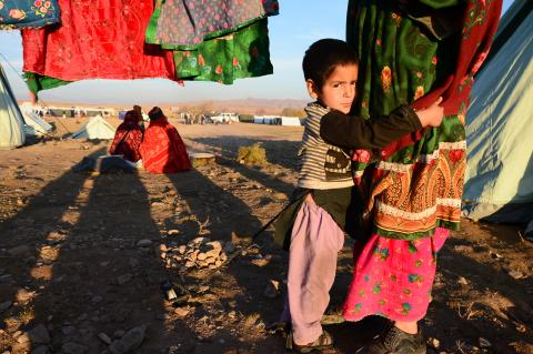 A displaced boy looks on while holding his mother in an IDP camp in Herat province of Afghanistan