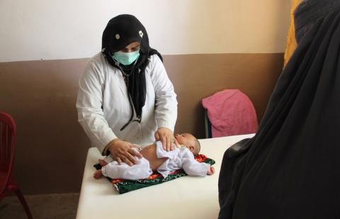A midwife checking a baby's umbilical cord care
