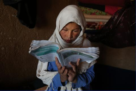 Robaba, 16, prepares diligently for tomorrow's classes in her new home in Yakawlang disctrict, Bamyan province.
