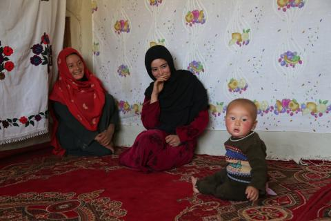 Kobra, 12, (centre) and her sister Zahra, 22, watch on as Zahraa's baby boy plays in their house in Daga village, central Afghanistan.