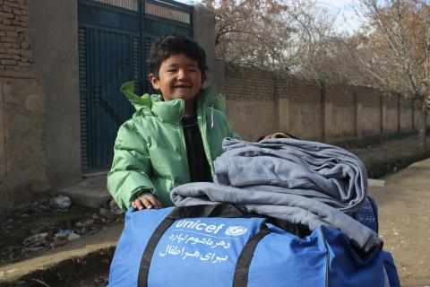 Mirwais, 8 years old, receiving his winter clothes distributed by UNICEF