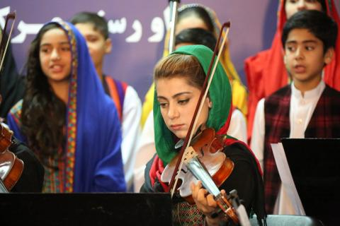 A girl playing violin during celebration if International Day of the Girl in Kabul