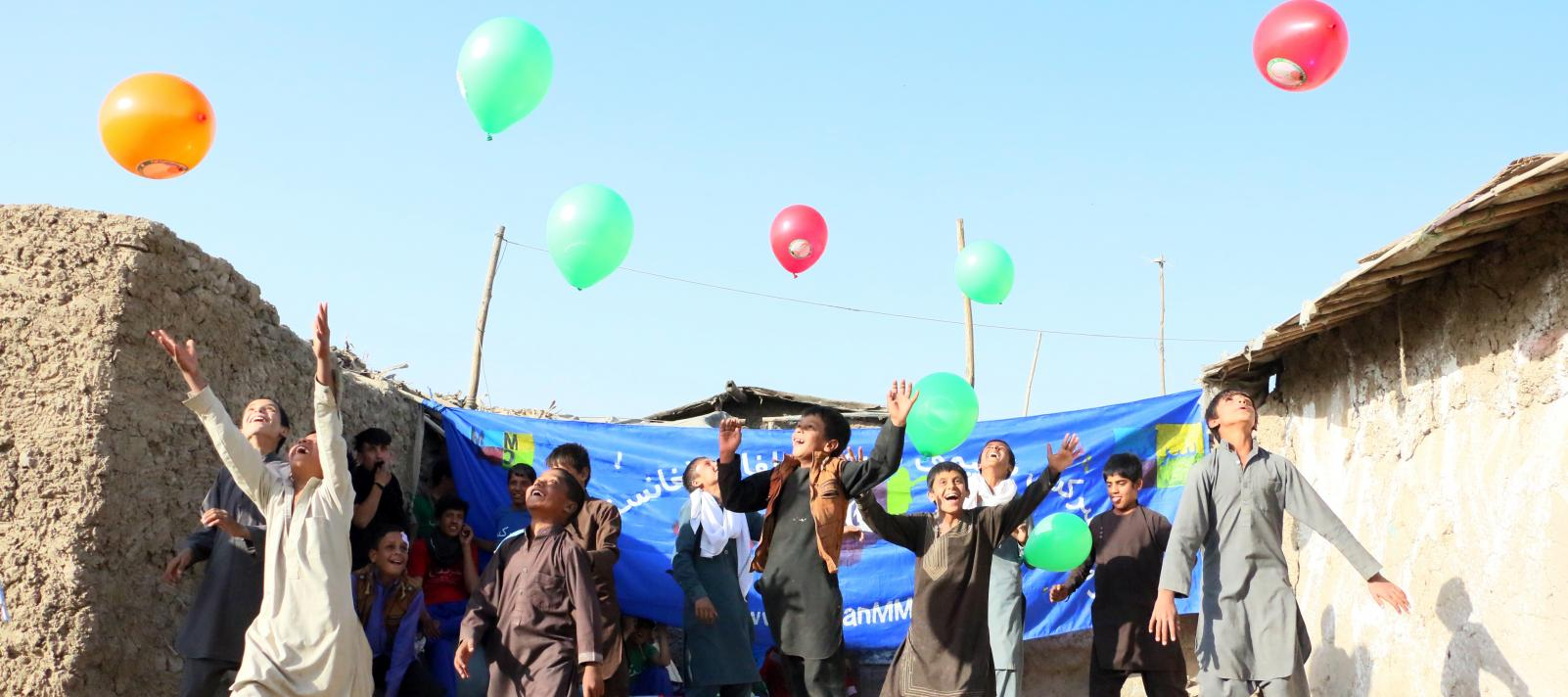 Children jump as they release balloons into the sky. Kabul, Afghanistan