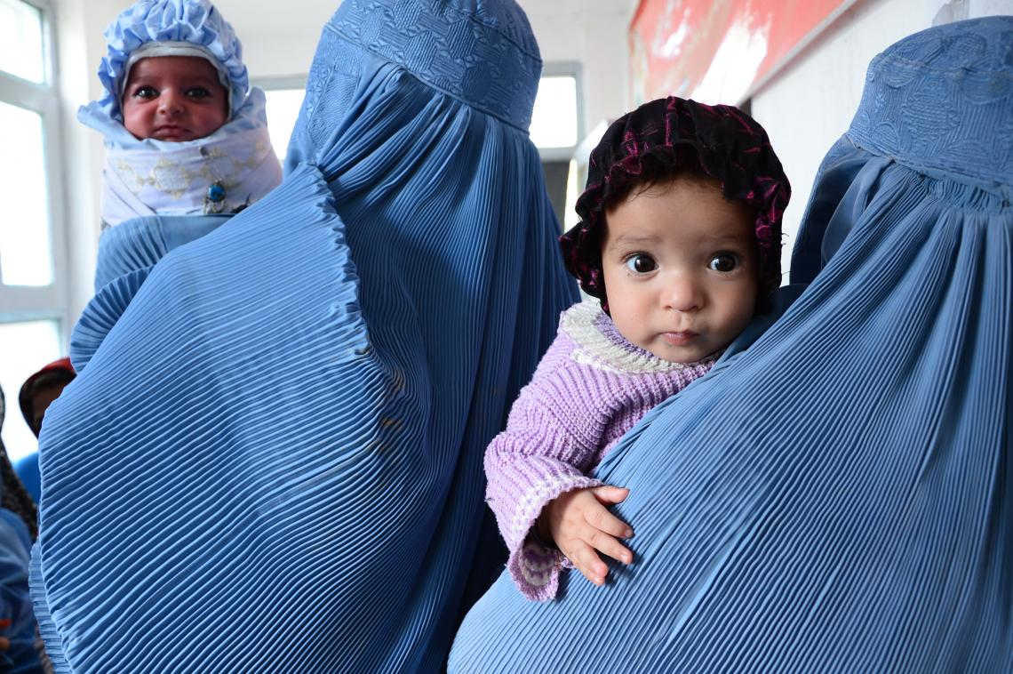 Afghan women clad in burqas hold their babies while they wait to get their children vaccinated in a hospital supported by UNICEF in the Guzzarah district of Herat province.