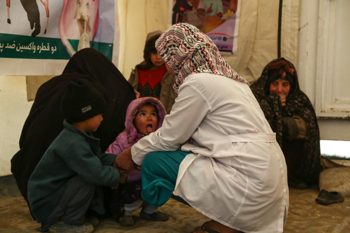 Sima, providing counseling on breastfeeding to mothers and playing with children visiting the clinic with their mothers. 5-year-old Abdul Rahman and 3-year-old Fariba visiting the clinic are suffering knee pain.