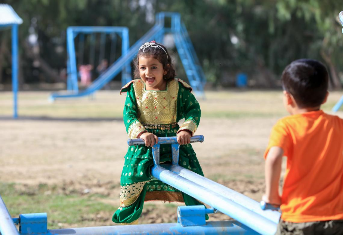 A girl in green plays on a swing in a 'safe play area' park in Kandahar, Afghanistan.