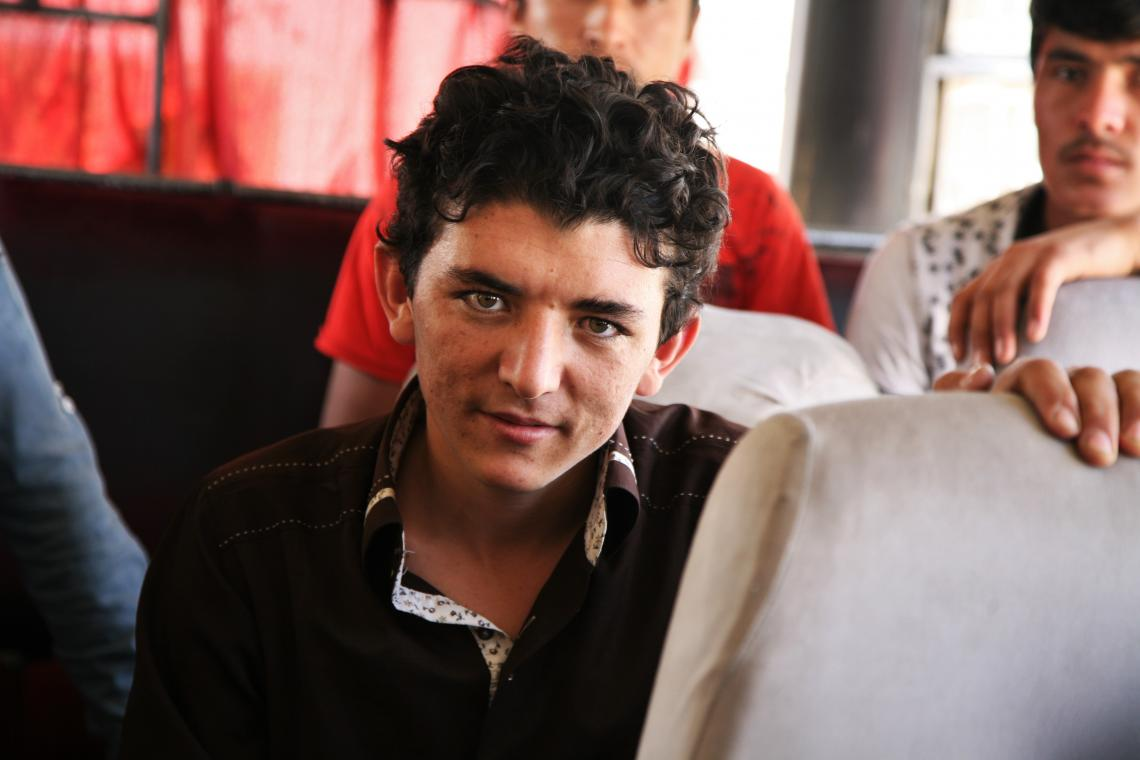 A young male unaccompanied minor poses for photo on a bus at the border between Iran and Afghanistan.