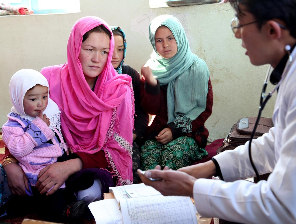 A mother and her children sit with a doctor during a consultation with a UNICEF-supported mobile health team in Bamyan, Afghanistan.