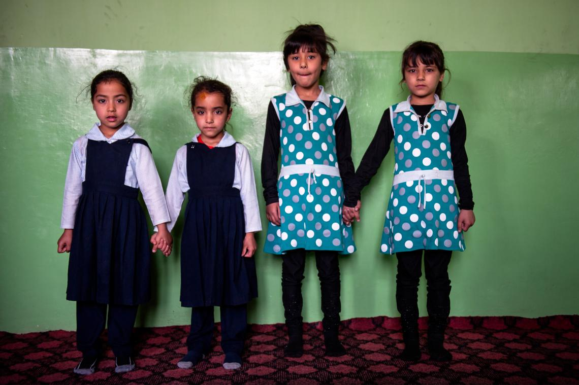 Two pairs of twin girls, all five years old, hold hands standing in front of a painted wall inside a children's day care centre in Kabul, Afghanistan. The girls on the left are shorter and stunted.