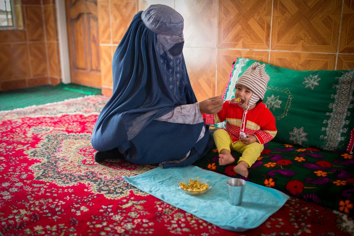 A woman in a burqa feeds her 15-month old daughter in Mazar-e-Sharif, northern Afghanistan.