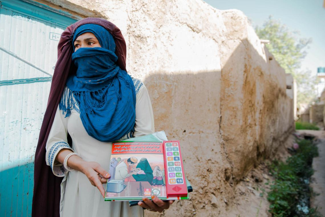 A female social mobilizer in Kandahar, Afghanistan, holds an audio book used to explain the importance of polio vaccinations