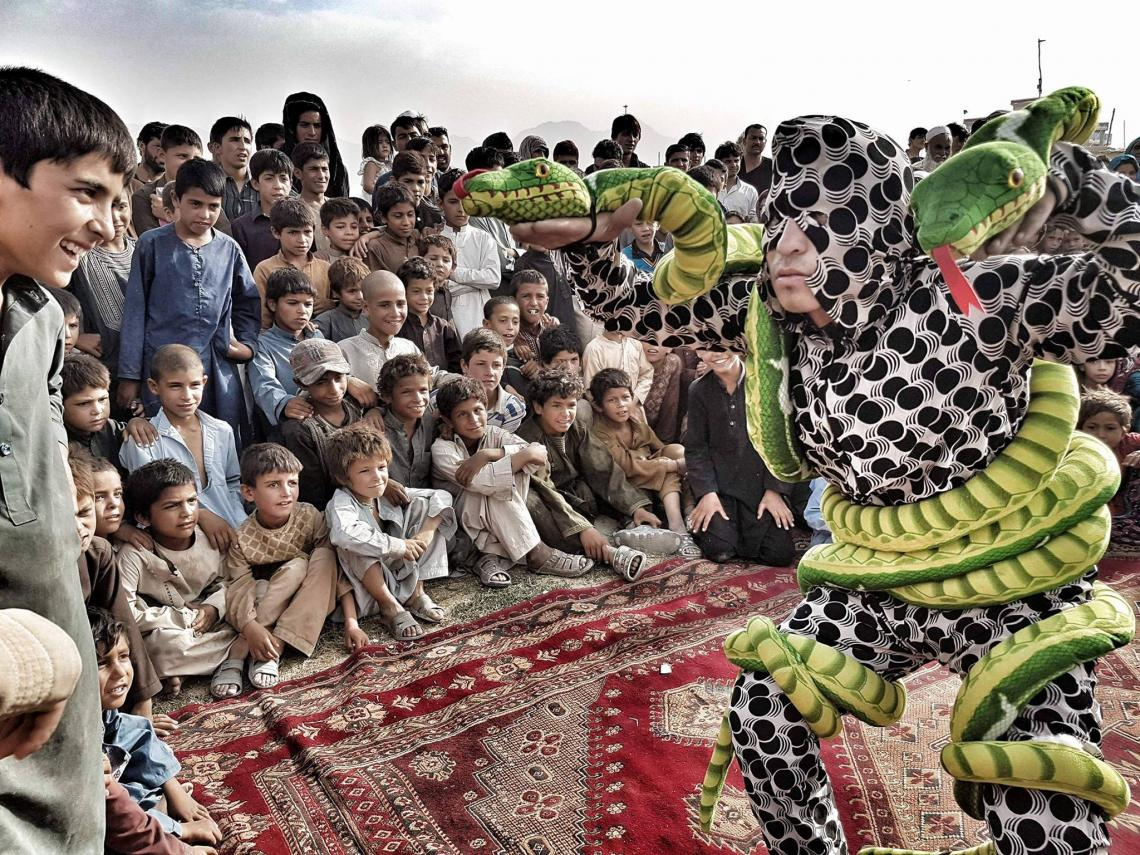 A theater show at a camp for internally displaced persons in Kabul, Afghanistan: Two snake puppets representing the polio virus are about to be destroyed by a vaccinator armed with two drops of vaccine.