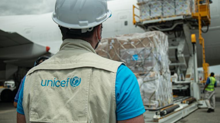 One UNICEF employee looking at goods being discharged from a cargo plane on a tarmac