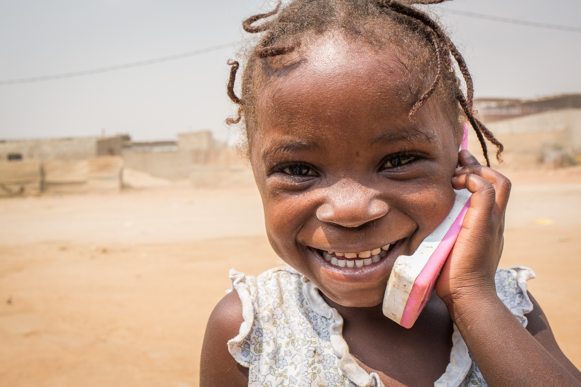 Girls plays with a mobile phone toy, pretending to speak to someone, during a polio immunization campaign in Angola, in 2015