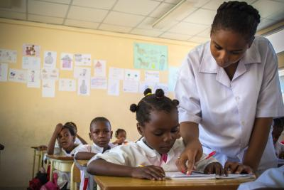 Teacher explains lesson to girl student in primary education classroom