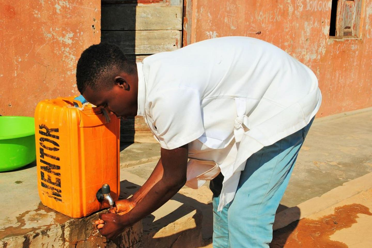 Student Graça Francisco washes his hands in a tip tap of a Child Friendly School in Cuito, Bié Province