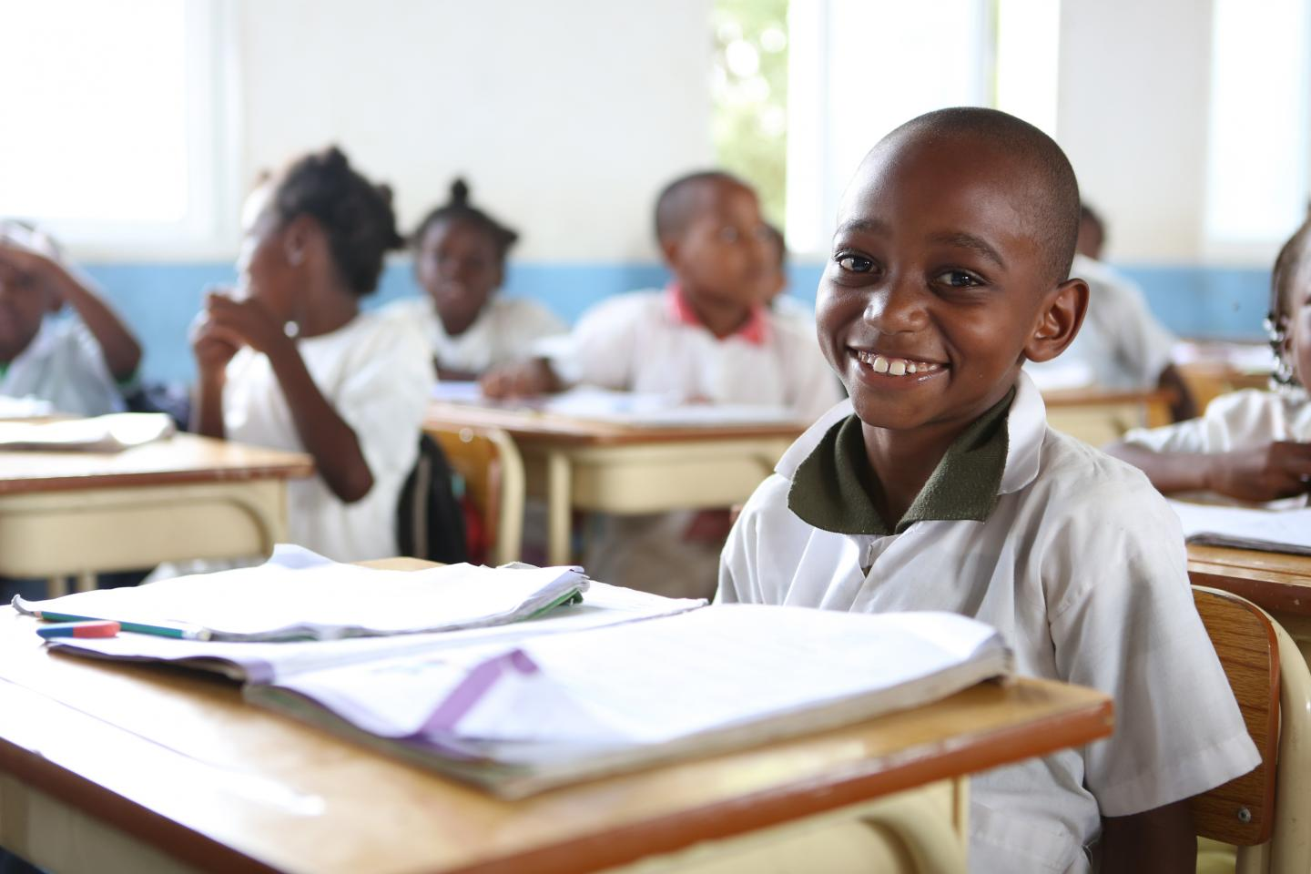 Boy smiles to camera in a classroom in Cacuaco Municipality, Luanda Province