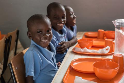Boys smile while having a school meal in Luanda