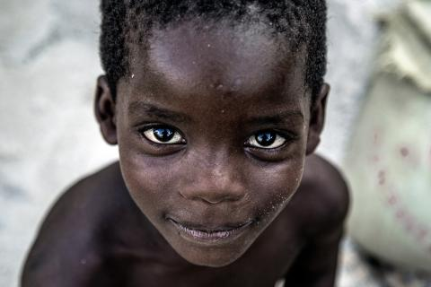 Boys looks to the camera in close up, in Angola