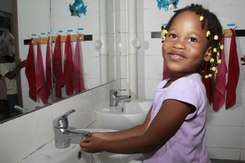 Girls washes her hands in school toilet