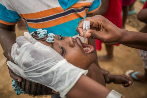 Girl child opens her mouth to receive drops of polio vaccination