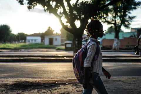 Student girl walks back home after school in street during sunset in Luena, Moxico Province