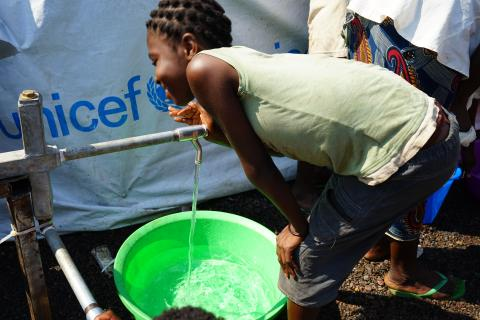 Children carrying water in refugee camp in Dundo