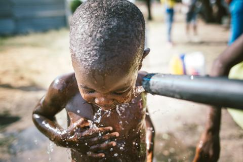 Boy showering in a water pump installed by a UNICEF Angola WASH project