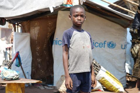 On 30 May 2017, a boy stands in front of a tent covered with canvas provided by UNICEF in the Mussungue reception centre for refugees in Dundo, northern Angola.