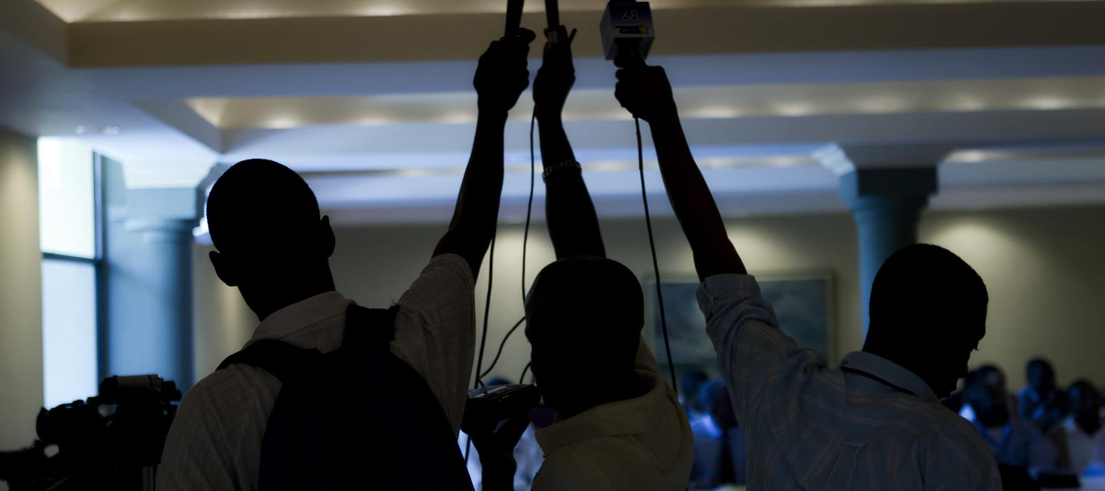 Journalists hold up microphones to record a speech in a press conference