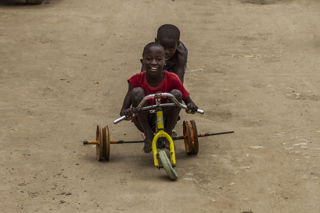 A boy pushes his friend in a tricycle made of reused parts