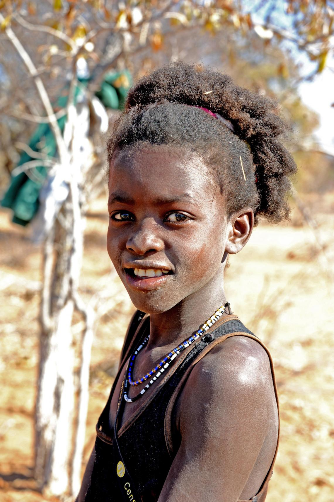 12-year-old Marta Ndimaoshitya and her six other siblings share and alternate the task of accompanying their father on the 1-hour-long daily to fetch water in Cuene province, Southern Angola.
