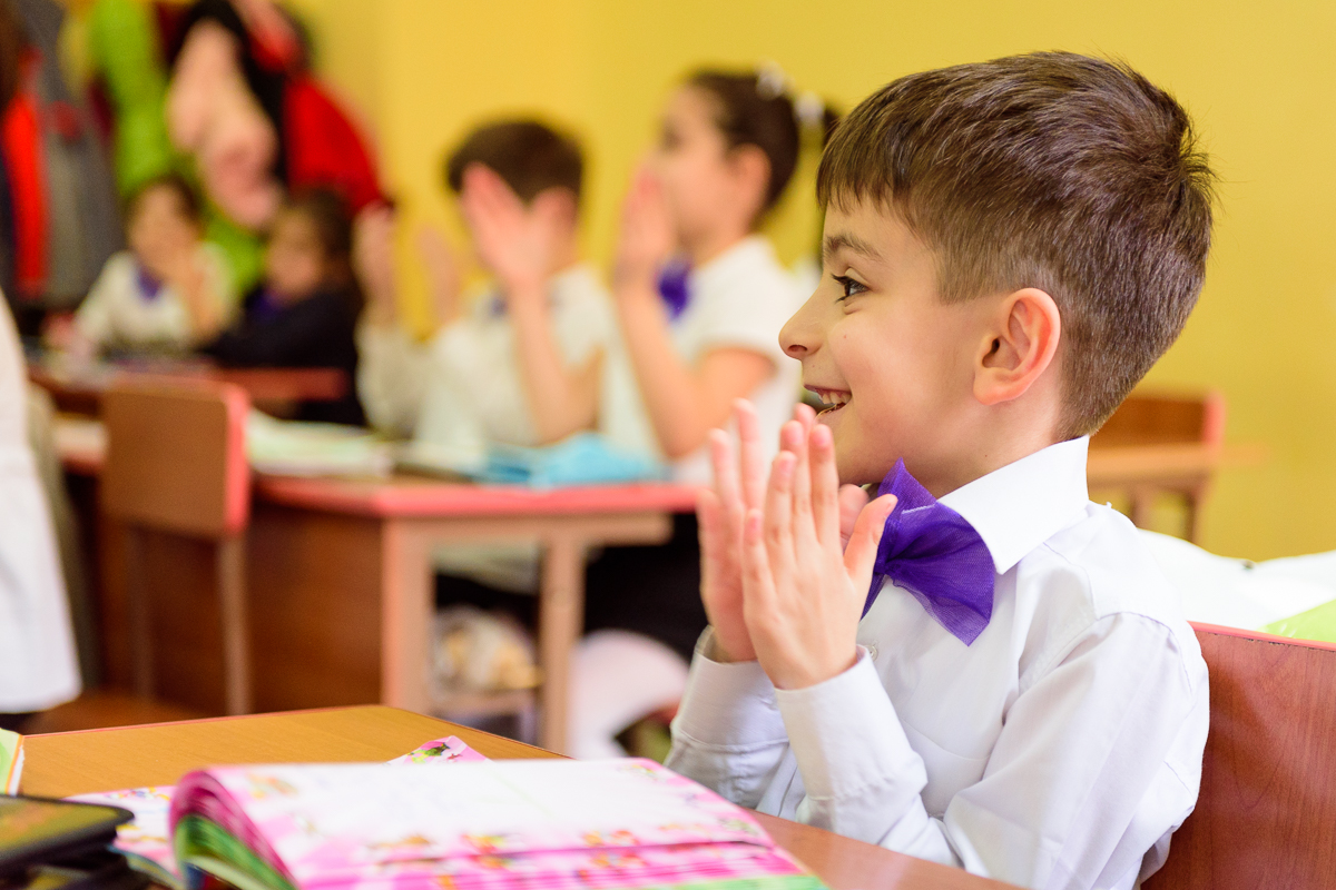 A boy with a purple bow over his white shirt claps his hands and smiles in the classroom during the lesson.