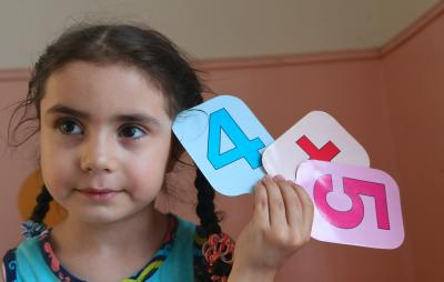 A girl holds numbers in class during a session.