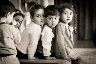 3 children in inclusive kindergarten sitting on the bench.