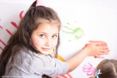 A 5 year old girl in the alternative preschool staring to camera while painting her hand.