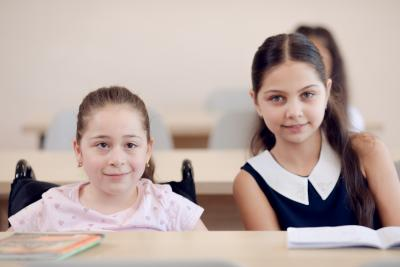 Two girls with and without disabilities sit together at the same desk in the classroom