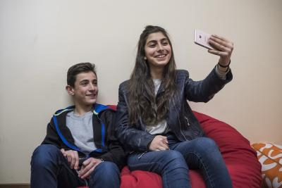 Brother and a sister are taking a selfie to share via social media channels.