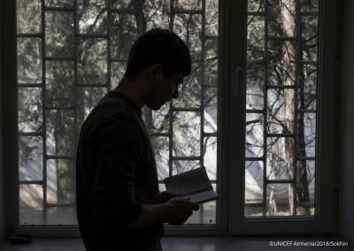 "A 17-year old boy reading poems by a window in a room of ""Noubarashen"" penitentiary institution for adolescents."