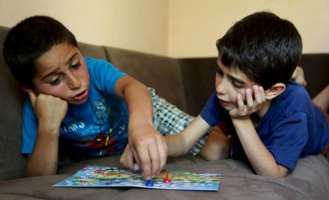 Two boys are playing a board game and talking to each other on the sofa in the Children's Development Center for children from disadvantaged families.
