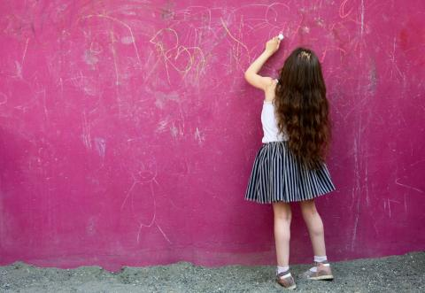 A girl writing on the pink board in the garden.