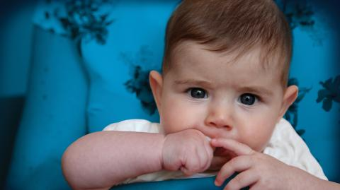 An 8 months old boy looking to the camera with his blue eyes and holding his hands in his mouth.