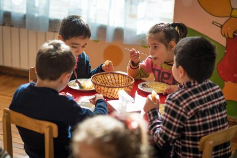 A meal time in the inclusive kindergarten. 4 children eating their meal with great appetite.