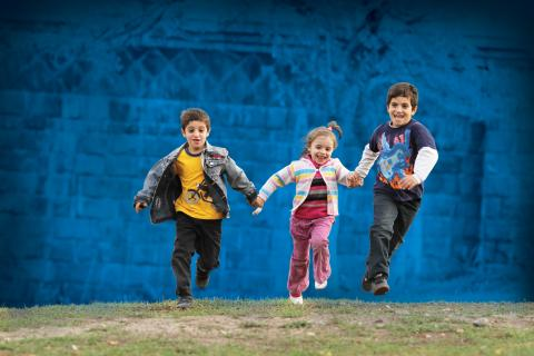Two boys and a girl are running hand in hand on the grass.